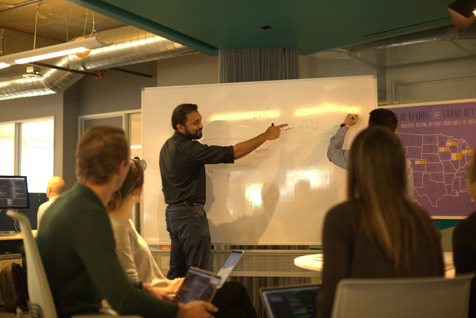 Man in front of whiteboard in group meeting