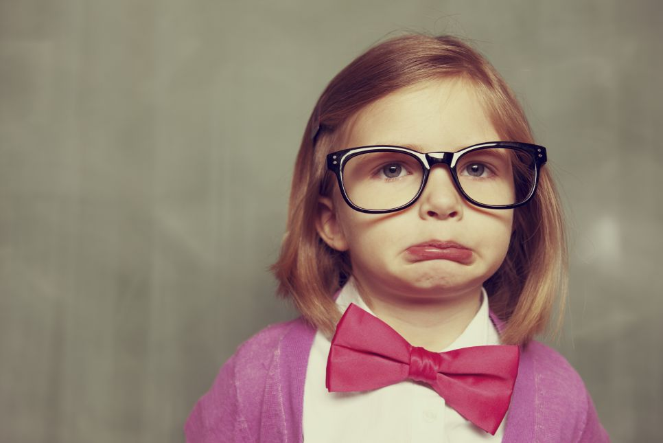 Young kid with oversized glasses and bow tie and pouty face