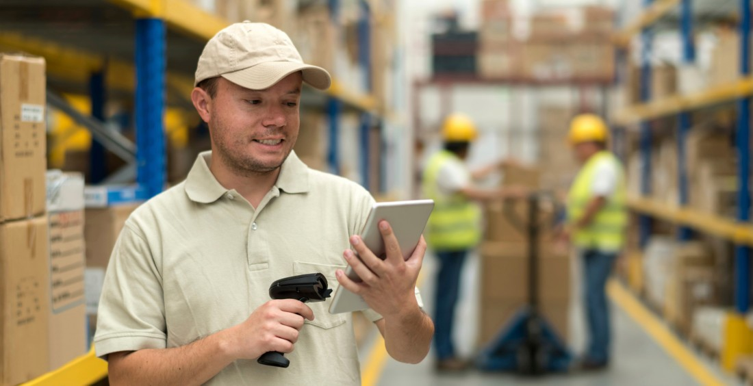 Man in warehouse with tablet and scanner
