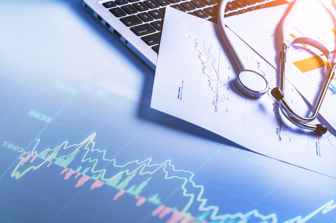 Stethoscope on laptop keyboard with financial report