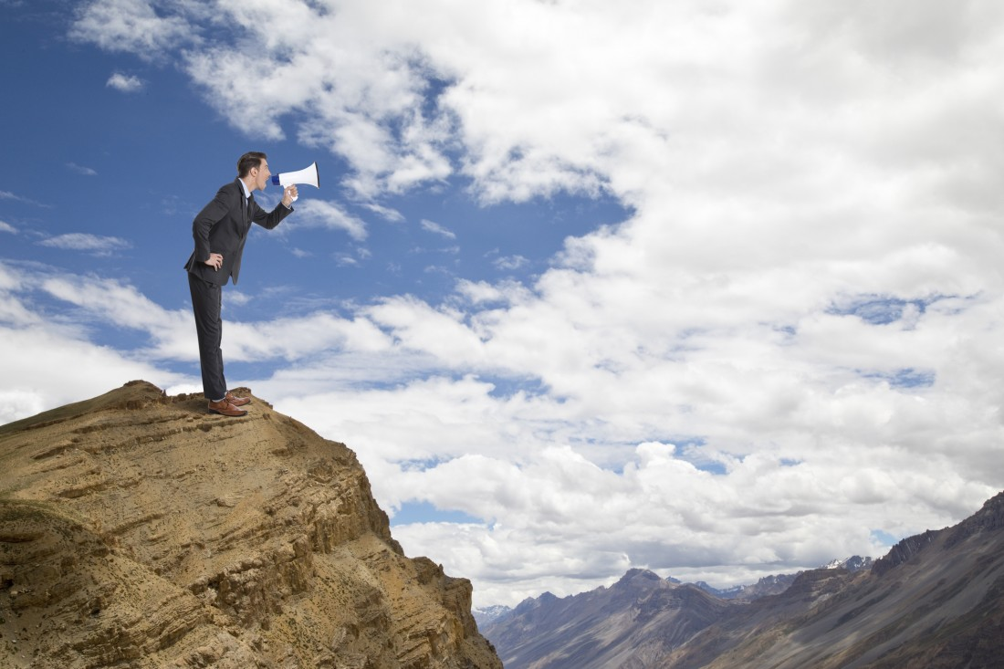 Businessman shouting on megaphone on top of cliff