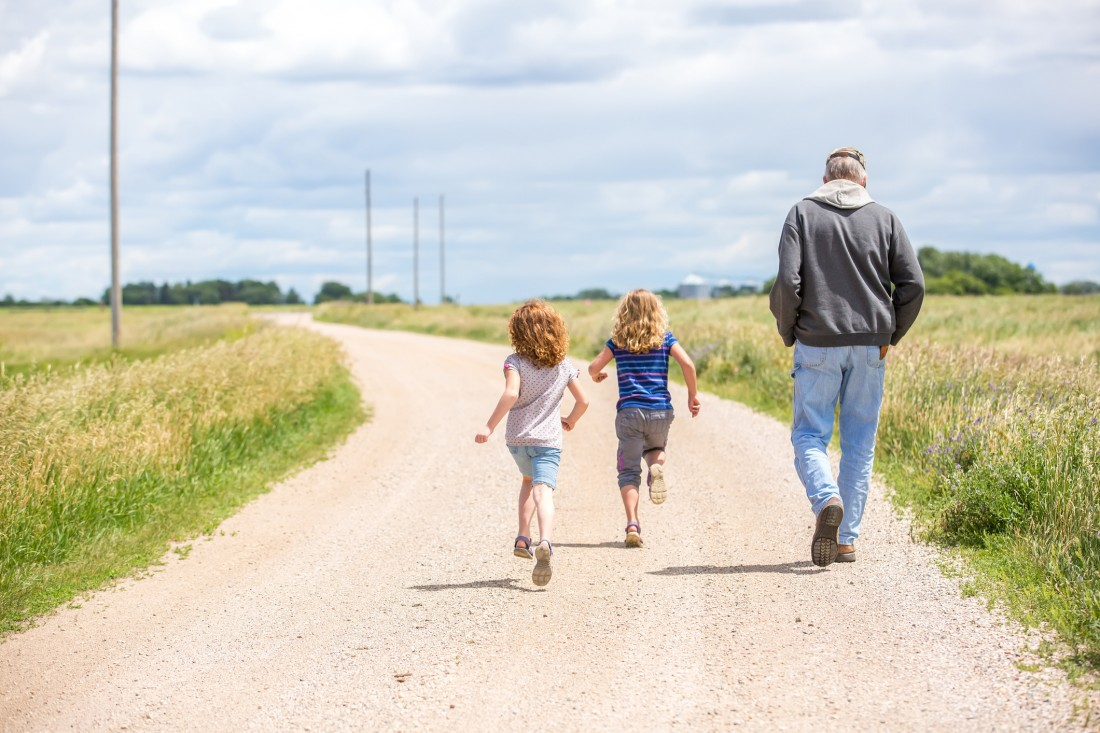 Rear view of two young girls running out a rural gravel driveway as Grandpa walks along with them. The older sister is in the lead and has curly blonde hair with a blue striped t-shirt and capris. The younger sister is following and has curly red hair. Taken on a sunny summer day in Minnesota, USA.