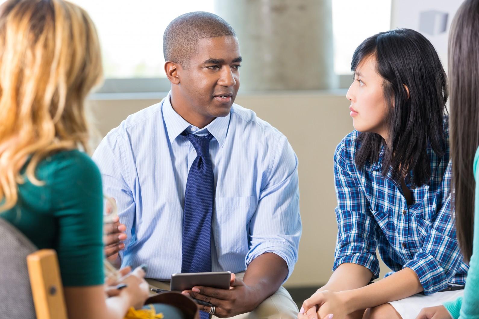 Mid adult African American man talks with patients in group therapy session. A young Hispanic and a young Asian woman listen intently to him as he speaks. He is taking notes on a digital tablet. The women are casually dressed. The man is wearing a light blue button down shirt and a tie.